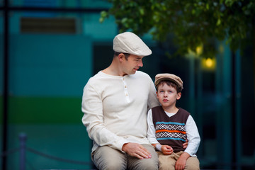 Happy father and son talking outdoors in city