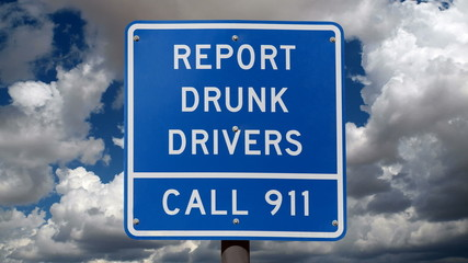 Report Drunk Drivers Sign with Time Lapse Clouds
