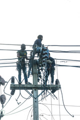 Three Asian electrician climb high in pole to work