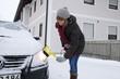 Junge Frau befreit Auto von Eis und Schnee