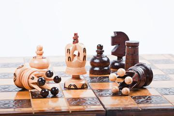 Triumphierender König zwischen gefallenen Schach-Figuren