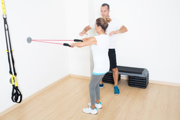 Trainer hilft älterer Frau mit Fitnessübung