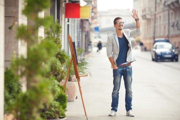 Cheerful young man waving on the street.