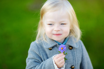 Adorable girl holding a flower