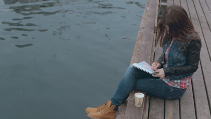 Cute girl sitting on a wooden pier near the sea and drawing