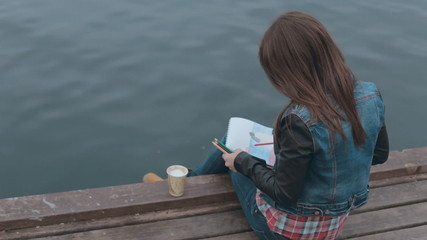 Charming girl sits on a wooden pier near the sea and drawing