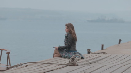 Romantic girl in skirt sitting on the pier near the sea and