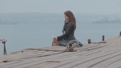 Close up of a cute girl sitting on the dock looking at the sea,