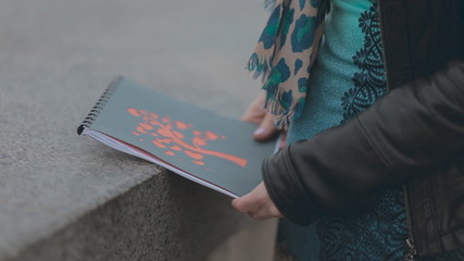 Close up of beautiful cover of album in the hands of girl