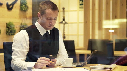Businessman comparing data on smartphone, documents and laptop