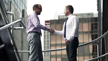 Businessmen talking, making deal and shaking hands in the city