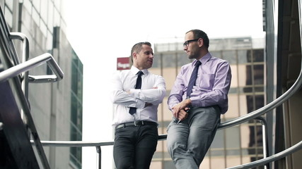 Two, young, handsome businessmen talking in the city