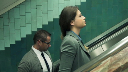 Two businesspeople with smartphone riding up on escalator