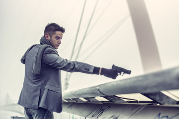 Young detective or policeman or mobster firing a gun
