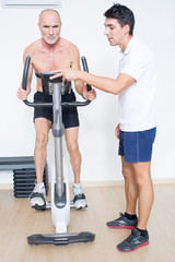 Fitnesstrainer beim Leistungstest im Fitnessstudio