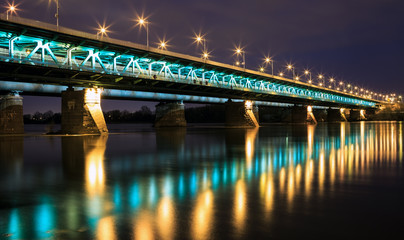 Highlighted bridge at night and reflected in the water.Bridge Gd