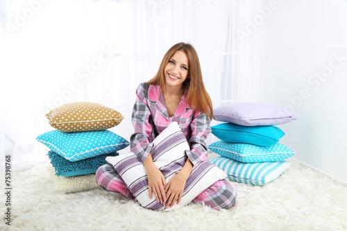 Leinwandbild Motiv Beautiful young girl with pillows  on light background