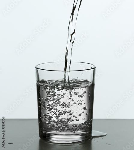 wylewanie-wody-z-butelki-na-szkle-na-bialym-tle-na-wh