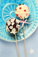 Tasty cake pops on plate, close up