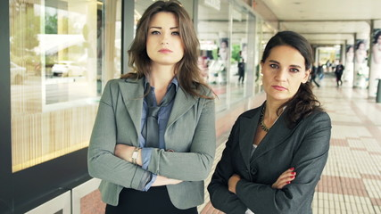 Portrait of two serious businesswomen looking at camera