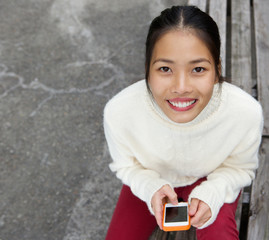Attractive young woman smiling with mobile phone