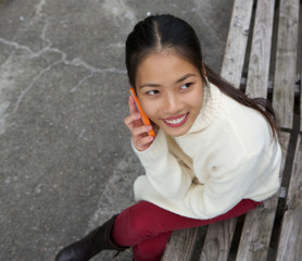 Young woman sitting on park bench and calling by mobile phone