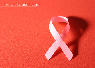 Pink breast cancer ribbon on red background