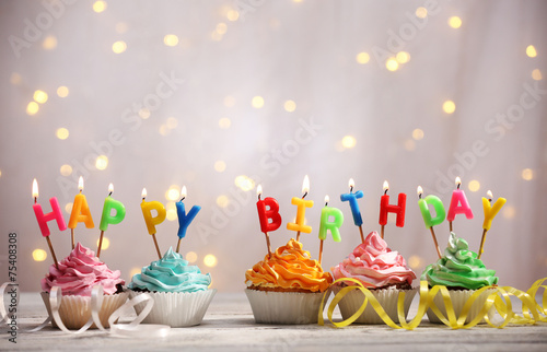 Delicious birthday cupcakes on table on light background - 75408308