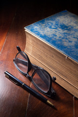 Antique book with eyeglasses and pen.