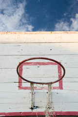 Old basketball hoop with blue sky