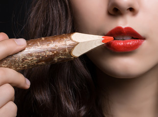 Woman paints her lips with a red pencil.