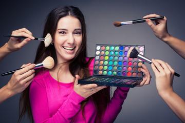 Cute make-up artist holding her vast palette of colors