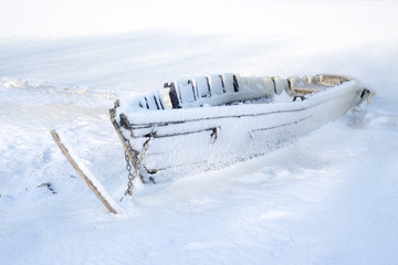 Coastline with old boat and snow all over