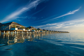 Over water villas in Maldives reflected in blue lagoon