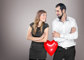 couple with heart balloon between them in studio