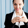 Happy businesswoman with laptop drinking coffee at office
