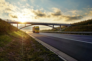 Sunset over highway, bridge and riding a yellow truck
