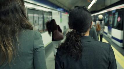 Two businesswomen walking and leaving metro platform