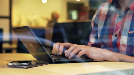 Male hands typing on laptop in cafe