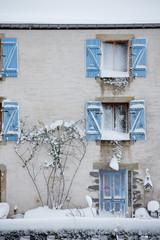 Maison au volets bleus enneigée