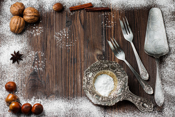 silver cutlery for dessert on a dark wooden background