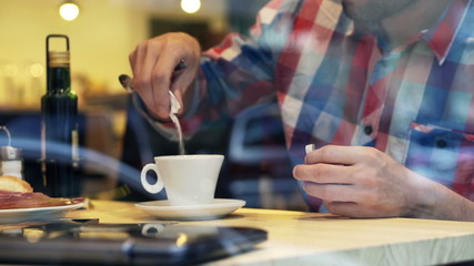 Man hands adding sugar into tea in cafe