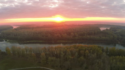 Red sunset, river and wood. .Aerial  lateral flight