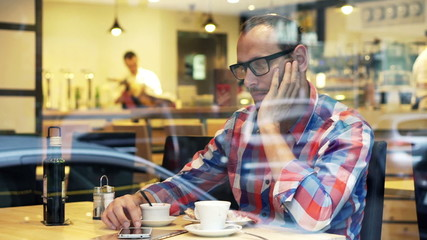 Young impatient man waiting for someone in cafe