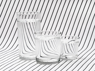 Three glasses of drinking water on striped tablecloth