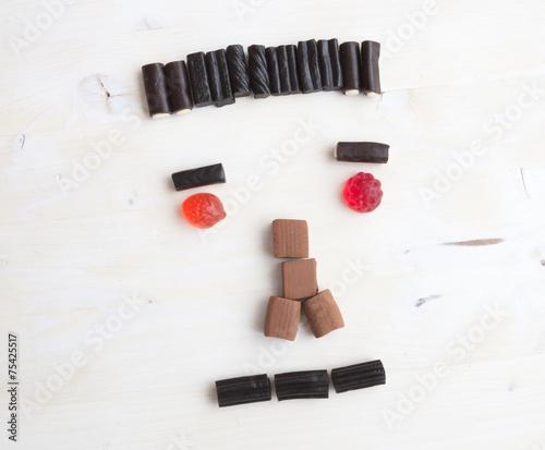 canvas print picture Neutral schauender Mann aus Süßigkeiten