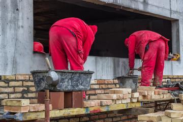 Two mason bricklaying outdoors