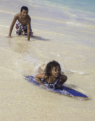 boy teaching sister to skim board