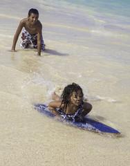 boy teaching sister to skim board