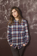 sad teenager girl in chequered shirt and jeans standing near bro